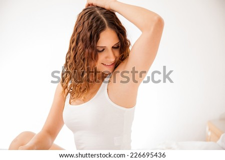 Pretty young brunette showing off her smooth and hair free armpits after hair removal - stock photo