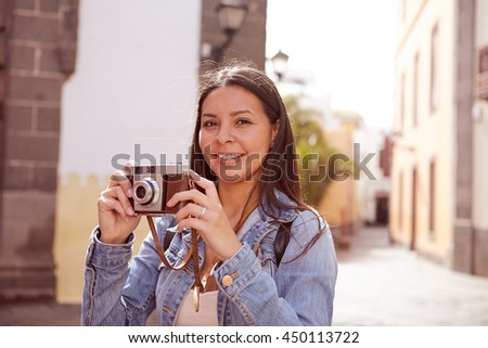 Pretty young brunette taking pictures and looking at the camera wearing her long hair loose and casual clothing with a narrow street in her background - stock photo