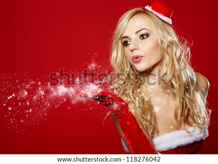 pretty young brunette woman dressed as Santa blowing on the snow on her hands - stock photo