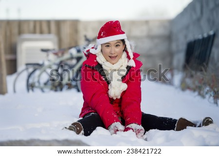 pretty young brunette woman dressed as Santa with snow