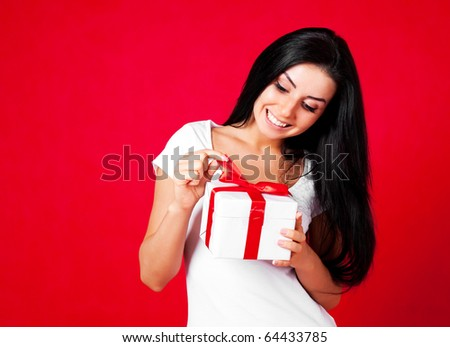 pretty young brunette woman dressed in red dress opening a present - stock photo