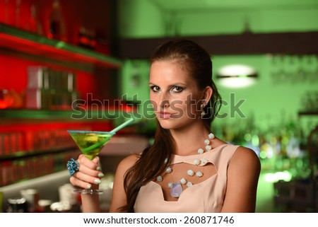 Pretty young brunette woman drinking cocktail in bar at night