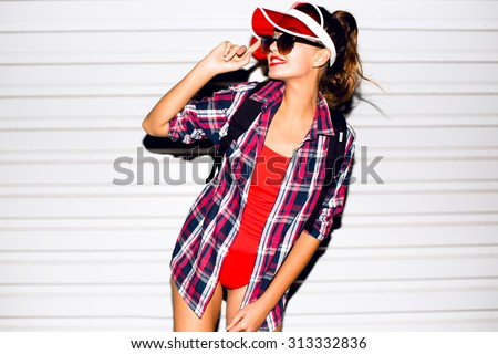 Pretty young brunette woman in glasses hipster style posing on red wall background closeup fashion portrait showing tongue with ice-cream,Neon Cap,hipster clothes,ponytail.travel bag,toned,soft photo - stock photo