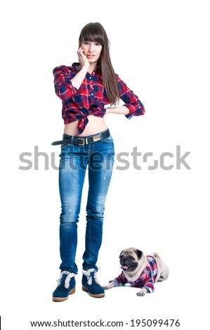 Pretty young brunette woman model with long straight hair standing together with her friend pug dog pet, both wearing checked pattern shirts girl wearing jeans and cool winter shoes. Isolated on white - stock photo