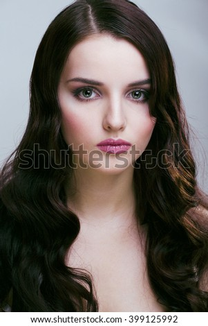 pretty young brunette woman with hair style like cute doll hairstyle waves, glamorous makeup - stock photo