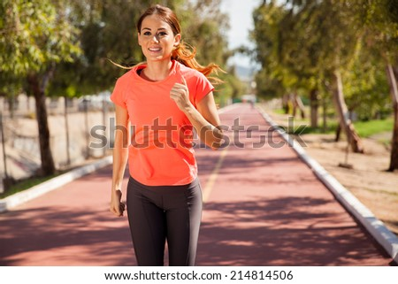 Pretty young brunette working out and running outdoors on a sunny day