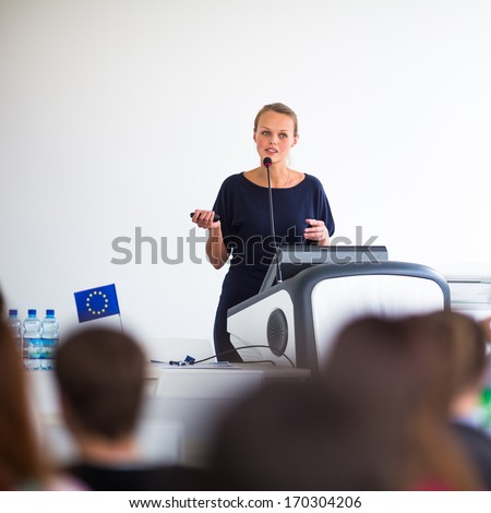 Pretty, young business woman giving a presentation in a conference/meeting setting (shallow DOF; color toned image) - stock photo