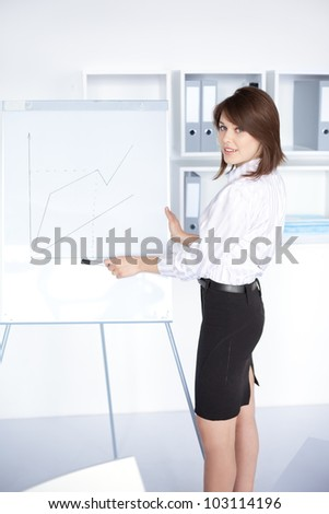 pretty young business woman presentation on flipchart at office - stock photo