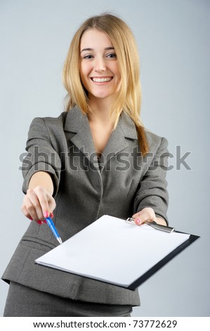Pretty young businesswoman asks you to sign paper - stock photo