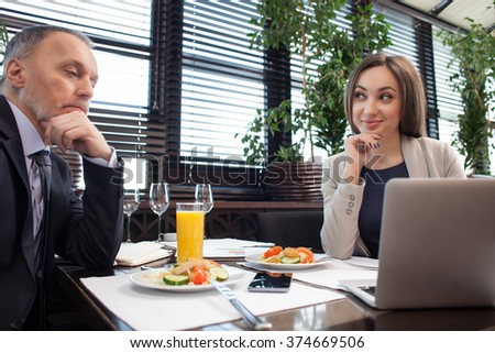 Pretty young businesswoman is showing to her client the result of her work. She is sitting at the table in restaurant and smiling proudly. The businessman is looking at the laptop seriously - stock photo