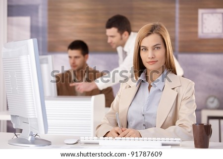 Pretty young businesswoman participating at training course, smiling.? - stock photo