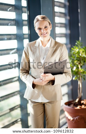 pretty young businesswoman standing by office window - stock photo