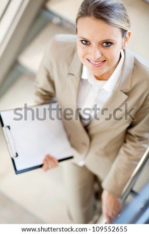 pretty young businesswoman standing on stairs and looking up