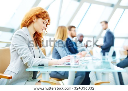 Pretty young businesswoman typing on laptop - stock photo