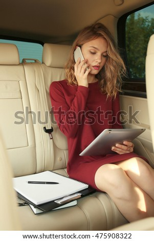 Pretty young businesswoman using mobile phone on car backseat