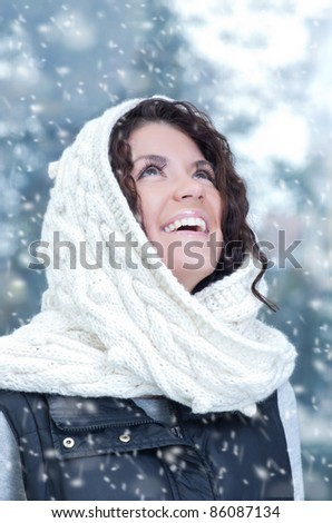 Pretty young caucasian brunette woman wearing white scarf with hood in a outdoor winter portrait - stock photo