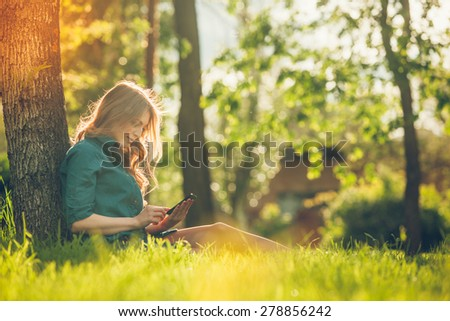 Pretty young caucasian woman  sitting outside under a tree talking on a smartphone device. Filtered effects - stock photo