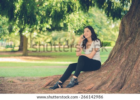 Pretty young caucasian woman wearing black jeans sitting outside under a tree talking on a smartphone device. Filtered effects - stock photo