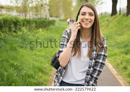 Pretty young Caucasian woman with backpack speaking on the phone outdoors in park laughing. Cute teenage girl with checkered shirt and long blonde hair talking on smart phone. No retouch. - stock photo