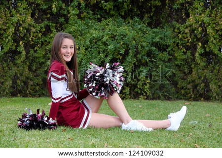 Pretty young cheerleader wearing a maroon colored uniform and pom-poms posing outdoors on lawn. - stock photo