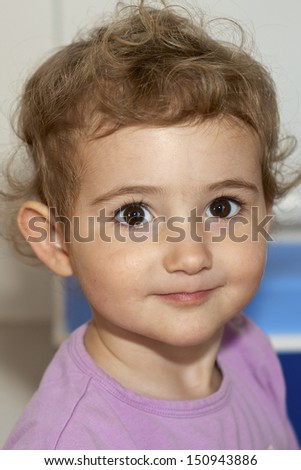 Pretty young child, girl toddler, playing indoors wearing purple lilac top. She is looking directly at camera with a hint of a smile on her face. She is smiling and has blonde curly hair. - stock photo