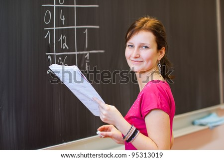 pretty young college student by the chalkboard/blackboard during a math class (color toned image) - stock photo