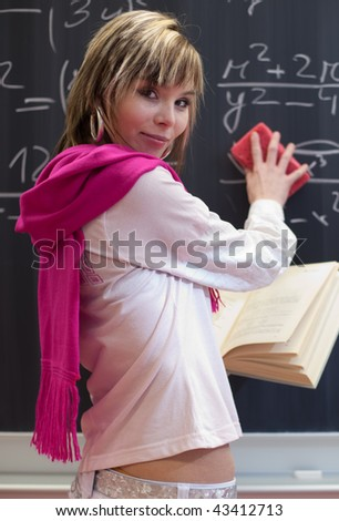 pretty young college student erasing the error she has just made in a math equation on chalkboard/blackboard in a classroom - stock photo