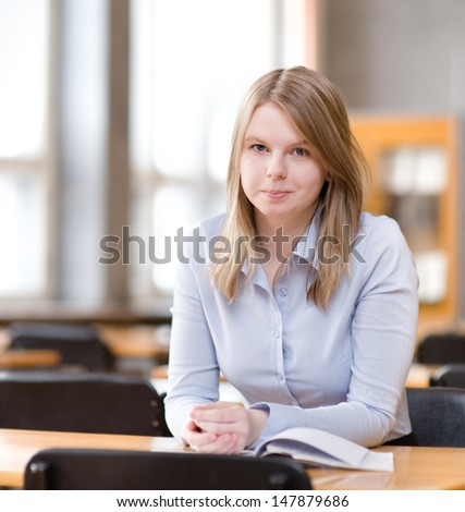 pretty young college student in a library - stock photo