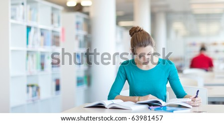 pretty young college student in a library (shallow DOF; color toned image) - stock photo