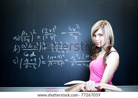 pretty young college student writing on the chalkboard/blackboard during a math class (shallow DOF; color toned image) - stock photo