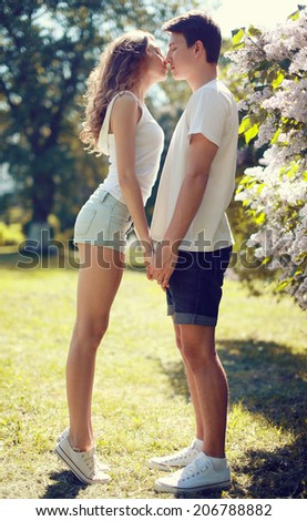Pretty young couple in love, sensual kiss in sunny warm day - stock photo