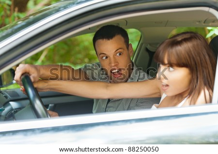 pretty young couple man woman sitting car surprised hold hands steering wheel background summer green park - stock photo