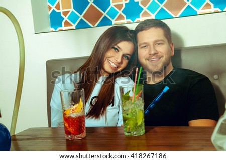 pretty young couple smiling on camera and smokes shisha in the bar - stock photo