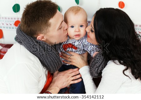 Pretty young couple, wearing in sweaters and jeans, sitting on the sofa and hugging little baby in decorated room, close up - stock photo