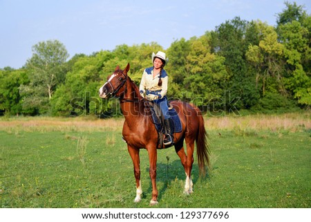 pretty young cowgirl riding horse - stock photo