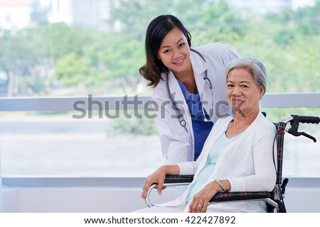 Pretty young doctor caring about elderly woman in wheelchair - stock photo