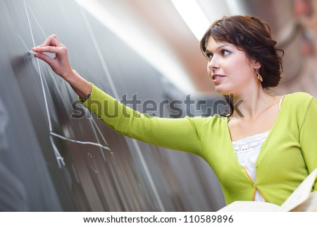 Pretty young elementary school/college teacher writing on the chalkboard/blackboa rd during a math class (color toned image; shallow DOF) - stock photo