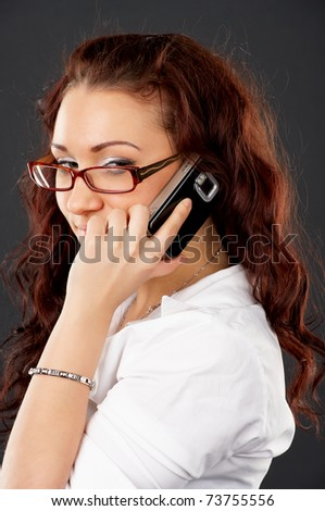 Pretty young executive talking on mobile phone against black background