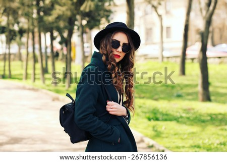 Pretty young fashion smiling blonde woman in sunglasses and vintage hat with leather bag posing outdoor in green park background in spring sunny weather. Fashion image of stylish hipster girl  - stock photo