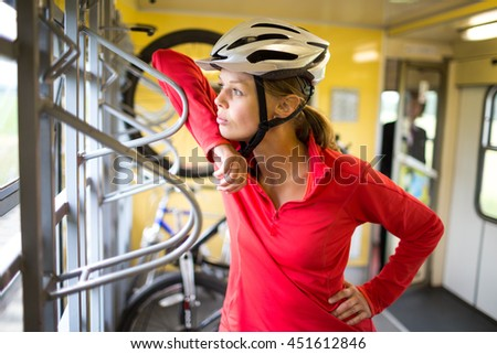 Pretty, young female biker outdoors on her mountain bike (shallow DOF; selective focus) - stock photo
