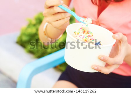 Pretty young female eating ice cream while looking away. Horizontal Shot. - stock photo