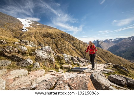 Pretty, young female hiker going uphill - stock photo
