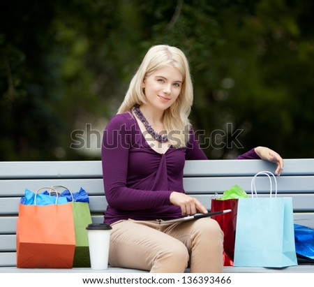 Pretty young female on city shopping trip taking a rest on bench with a digital tablet - stock photo