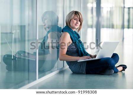 Pretty young female student with a laptop computer on college/university campus (shallow DOF; color toned image) - stock photo