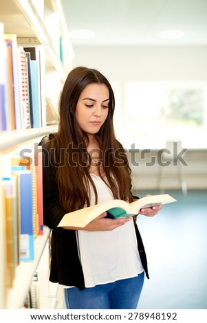 Pretty young female university student doing research in the library standing leaning against a bookshelf reading a book - stock photo