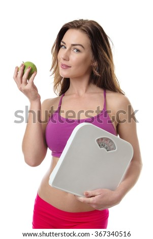 Pretty young fitness model holding a green apple and some weight scales isolated over white background - stock photo