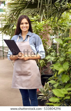 Pretty young florist with clipboard in greenhouse