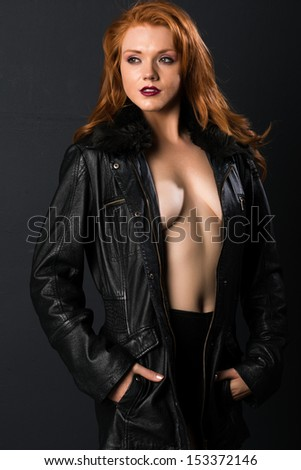 Pretty young freckled redhead in a leather jacket and shorts