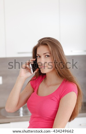 Pretty young girl communicates using a a mobile phone. Pretty woman calling by phone with her friends. - stock photo