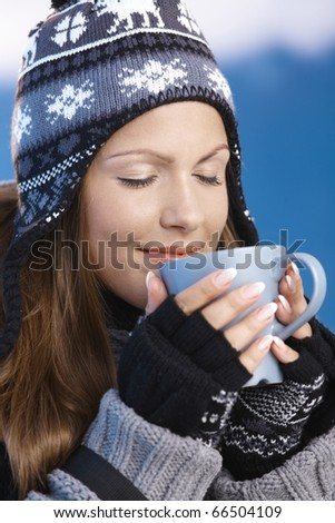 Pretty young girl dressed up warm for skiing wearing cap and gloves drinking hot drink eyes closed front of winter landscape .?